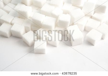 Sugar lumps stacked against a white background