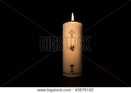 Holy candle with gold embellishment burning