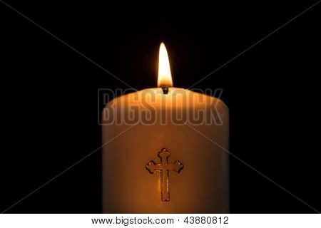 Candle with golden cross embellishment burning on black background