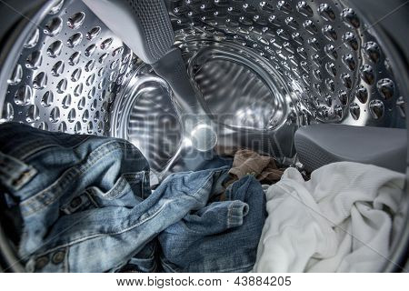 Internal view of washing machine drum filled with clothes