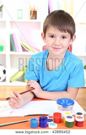 Cute little boy painting in his album