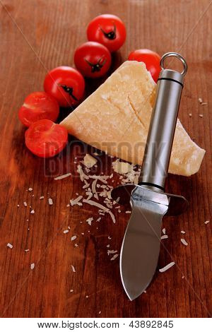 Piece of Parmesan cheese with knife on wooden table close-up