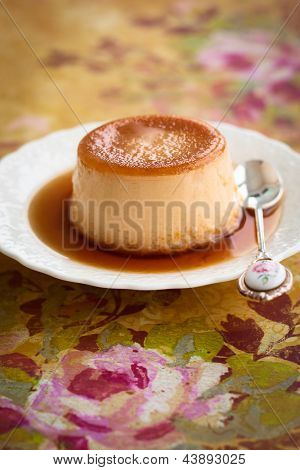 Creme caramel on plate with spoon