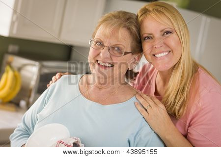 Smiling Senior Adult Woman and Young Daughter At Sink in Kitchen.