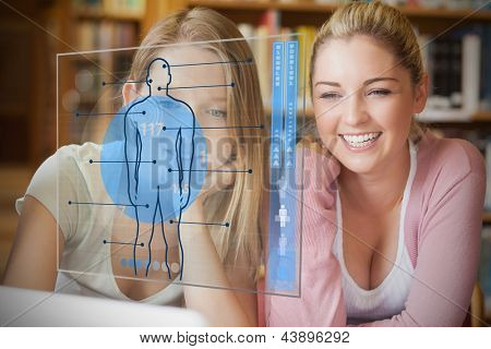 Two college students looking at laptop and futuristic interface with body diagram in blue