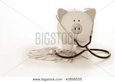 Piggy bank sitting on pile of dollars with stethoscope in black and white