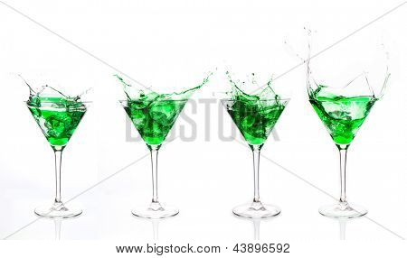 Serial arrangement of green liquid splashing in cocktail glass on white background