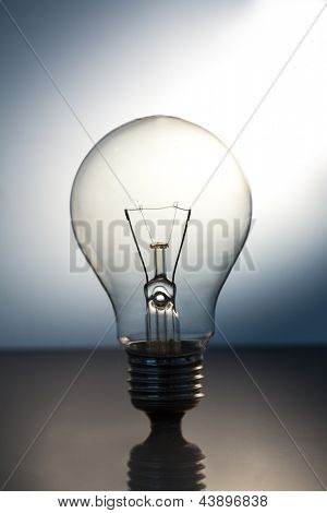 Big bright light bulb standing on a reflective suface