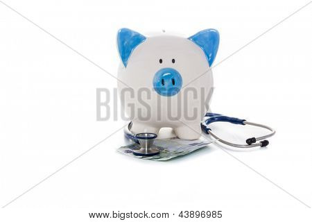 Hand painted blue and white piggy bank sitting on euro notes with stethoscope