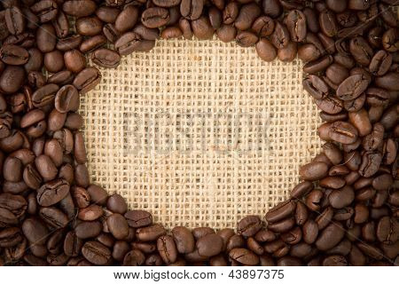 Coffee beans with oval indent for copy space on burlap sack