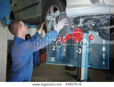 Mechanic checking wheel of a car helped by futuristic interface