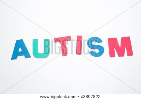 Autism spelled out in pink green and blue on white background