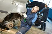 foto of peen  - auto repair man worker flatten and align metal body car with hammer in automotive industry - JPG