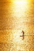 man paddleboarding in open water at sunset