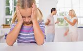 stock photo of depressed  - Little girl looking depressed in front of fighting parents in the kitchen - JPG