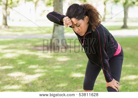 Tired healthy young woman taking a break while jogging in the park