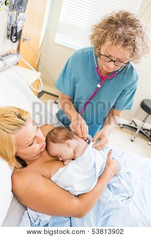 Mature nurse examining newborn babygirl with stethoscope in hospital room