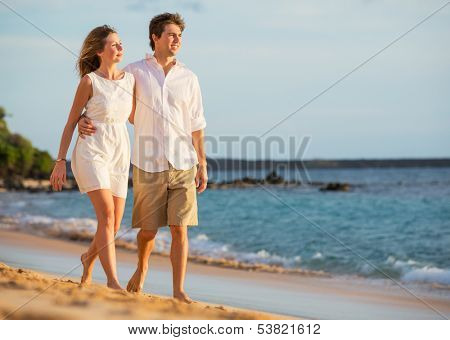 Romantic happy couple walking on beach at sunset. Smiling with arms around each other. Man and woman in love