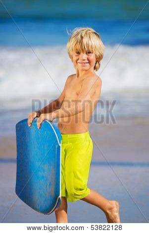 Happy Young boy having fun at the beach on vacation, with boogie board