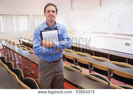 Portrait of a male teacher with notepad in the lecture hall