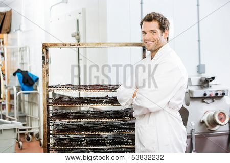 Portrait of happy male worker with arms crossed standing by rack of beef jerky at butcher's shop