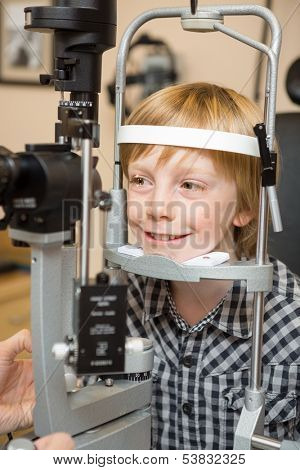 Smiling boy undergoing eye examination test with slit lamp in store