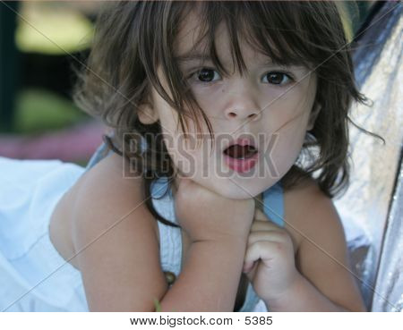 Child In Dress Laying Down Making Funny Face