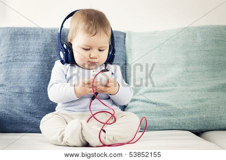 Cute baby boy sitting on sofa and listening music at headphones while  looking at iphone.