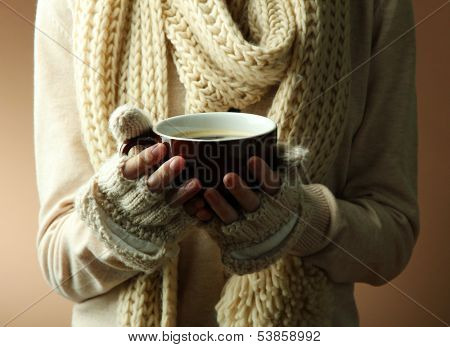 Female hands with hot drink, on color background