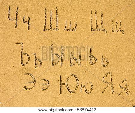 Russian alphabet (from Ch to Ja) written on a sand beach.