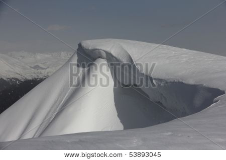 Snow cornice in mountains of Caucasus, Russia. Avalanche danger
