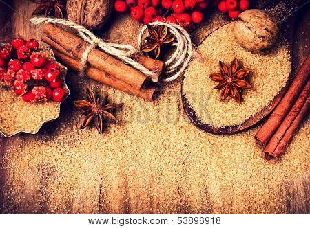 Christmas Background With Brown Sugar, Anise Star And Cinnamon Sticks On Wooden Table Close Up, Stil