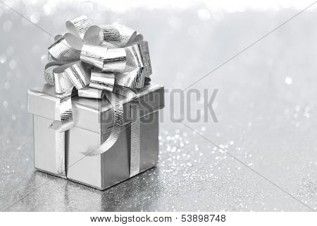 Silver holiday gift on glitter background