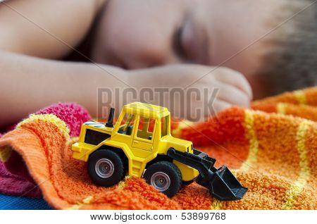 Rapaz dorme com escavadeira brinquedo