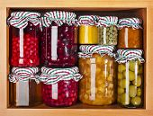 stock photo of pickled vegetables  - many glass bottles with preserved set food in wooden cabinet - JPG