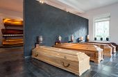 stock photo of urn funeral  - Wooden coffins standing in modern funeral house - JPG