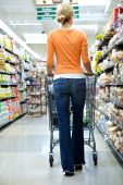 stock photo of grocery-shopping  - Supermarket Shopper in an orange shirt shopping for groceries - JPG