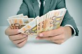 stock photo of bribery  - a man wearing a suit sitting in a desk counting euro bills - JPG
