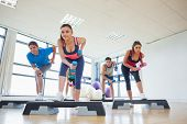image of step aerobics  - Full length of instructor with fitness class performing step aerobics exercise with dumbbells in a gym - JPG
