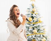 stock photo of christmas song  - Happy young woman singing near christmas tree - JPG