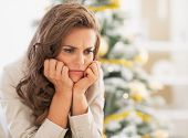 stock photo of sad christmas  - Portrait of frustrated young woman near christmas tree - JPG