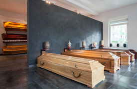 picture of urn funeral  - Wooden coffins standing in modern funeral house - JPG