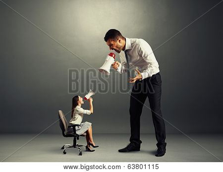 quarrel between small discontented woman and big man over dark background