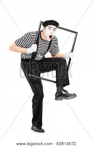 Male mime artist walking through a metal frame isolated on white background