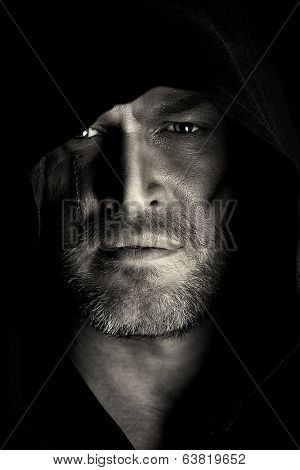 Portrait of a courageous warrior wanderer in a black cloak. Historical fantasy. Halloween. Black-and-white photo.