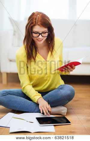 business, education and technology concept - smiling female student in eyeglasses with notebooks and tablet pc computer at home