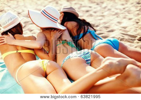 summer holidays and vacation - girls in bikinis sunbathing on the beach