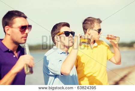 summer, holidays, vacation, happy people concept - group of friends having fun on the beach with bottles of beer or non-alcoholic drinks
