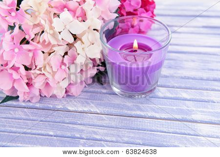 Beautiful colorful candles and flower,on color wooden background
