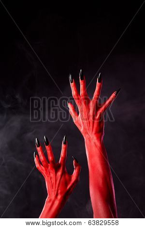 Horror red devil hands with black nails on smoky background, studio shot